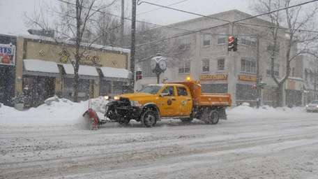 A plow truck moves snow down Main Street