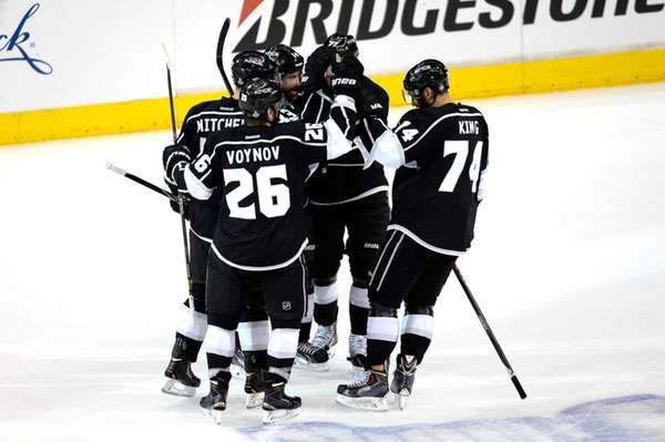 Willie Mitchell celebrates with his teammates after scoring
