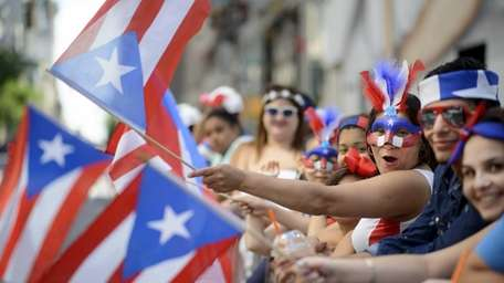 Revelers cheer and wave flags along 5th Avenue