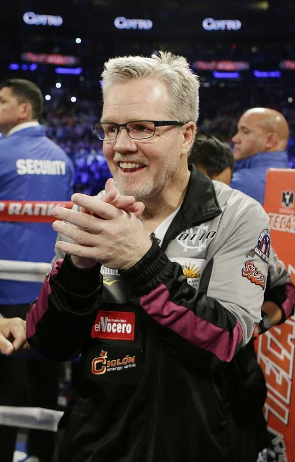 Miguel Cotto's trainer Freddie Roach celebrates after a