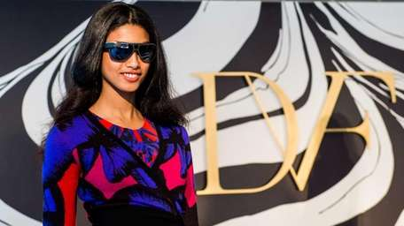 A model shows the DVF Aviator frame that