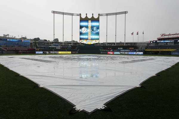 A tarp covers the infield as the rain