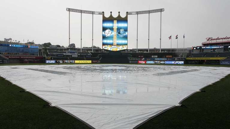 A tarp covers the infield as the rain