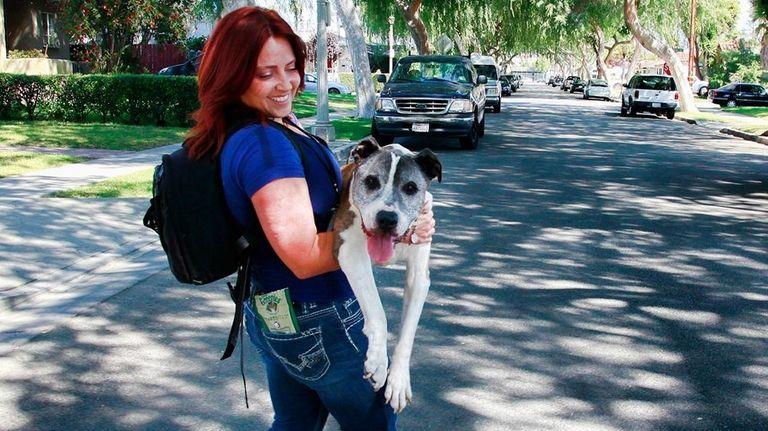 Lori Fusaro carries her senior dog Sunny, an