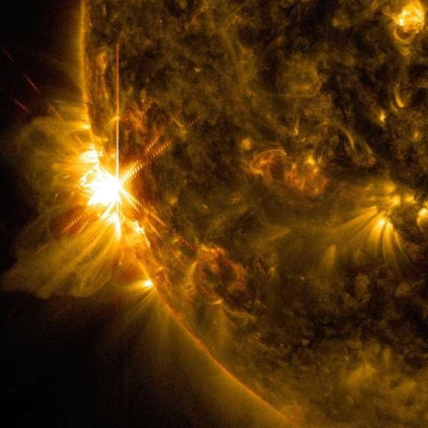 A solar flare bursts off the left limb