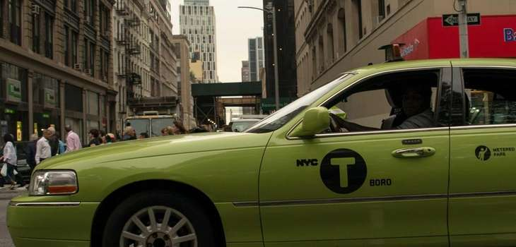 A green New York City taxi travels in