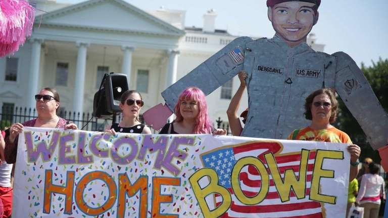 Activists hold a banner to welcome Army Sgt.