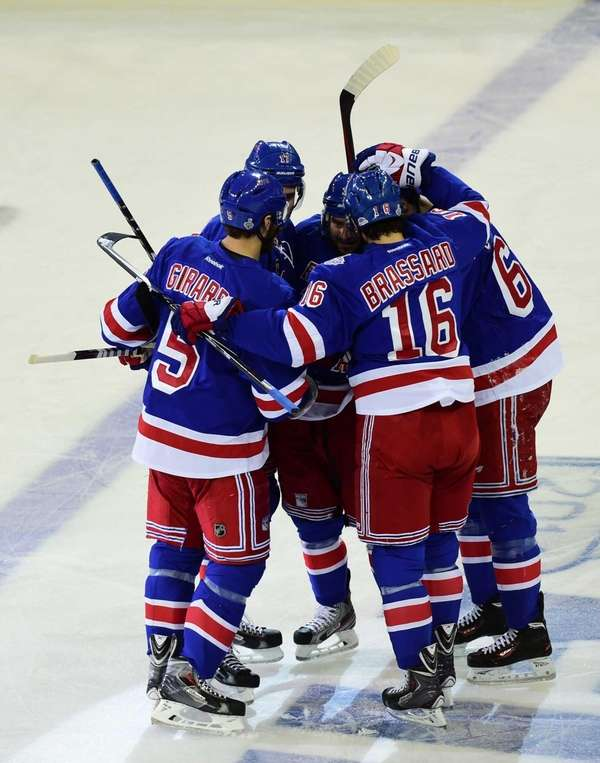 The Rangers celebrate left wing Benoit Pouliot's goal
