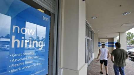 Shoppers walk past a now hiring sign at