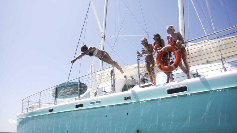 A woman dives off the catamaran Heron, which