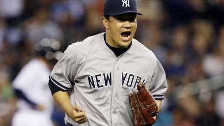 Yankees starting pitcher Masahiro Tanaka yells after the
