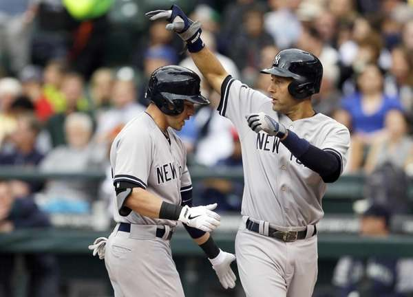 Yankees' Jacoby Ellsbury, left, is greeted at the
