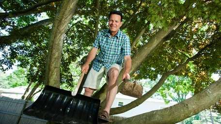 Timothy Kaler, 52, poses in a tree holding
