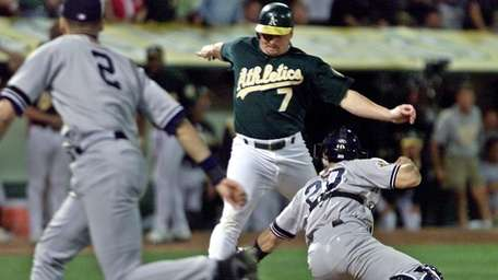 Oakland Athletics' Jeremy Giambi, center, is tagged out