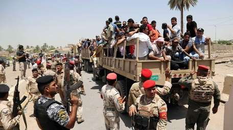 Iraqi men board military trucks to join the