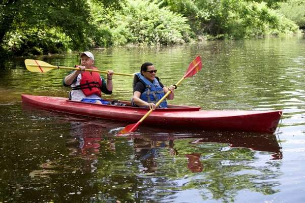 People ride in a canoe in the Nissequogue