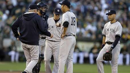 Yankees' Hiroki Kuroda is visited on the mound