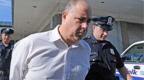 Thomas Stavola, 54, of Setauket, is led out