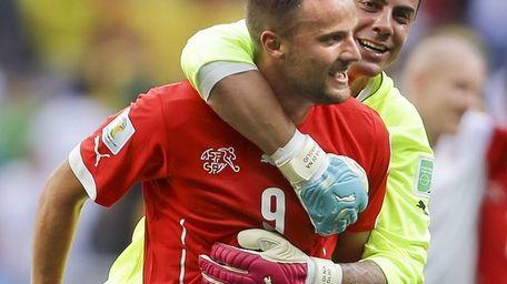 Switzerland's Haris Seferovic, front, and goalkeeper Diego Benaglio