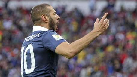 France's Karim Benzema celebrates an own goal by