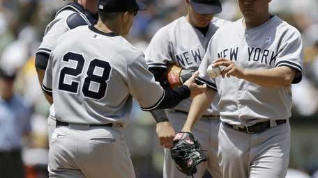 The Yankees' Vidal Nuno, right, hands the ball