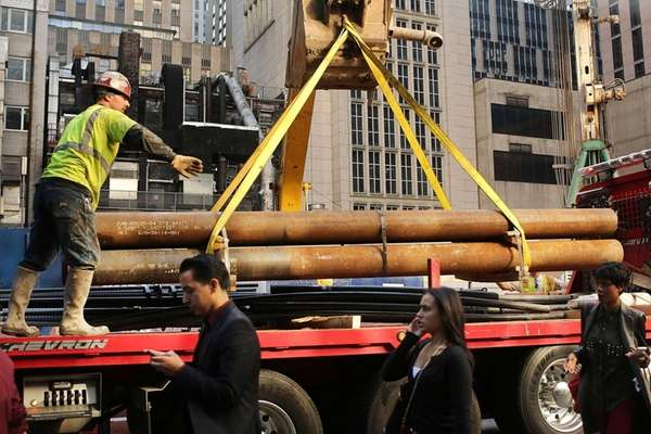 A construction worker moves pipes on a busy