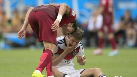 Portugal's Pepe, left, puts his head on Germany's