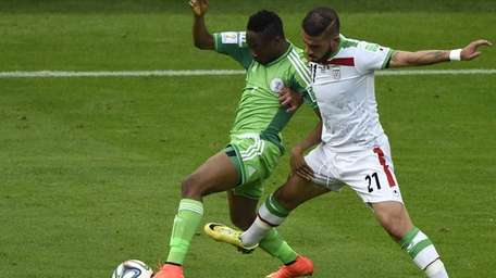 Nigeria forward Ahmed Musa, left, fights for the