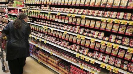 A shopper walks down the canned soup aisle
