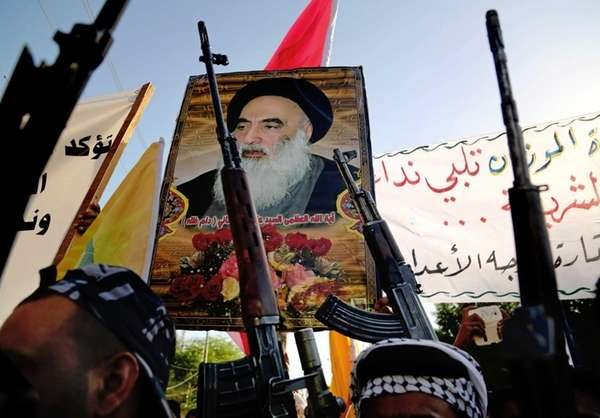 Shiite tribal fighters carry a poster of Shiite