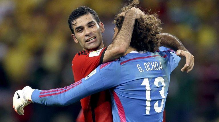 Mexico's Rafael Marquez, left, embraces Mexico's goalkeeper Guillermo