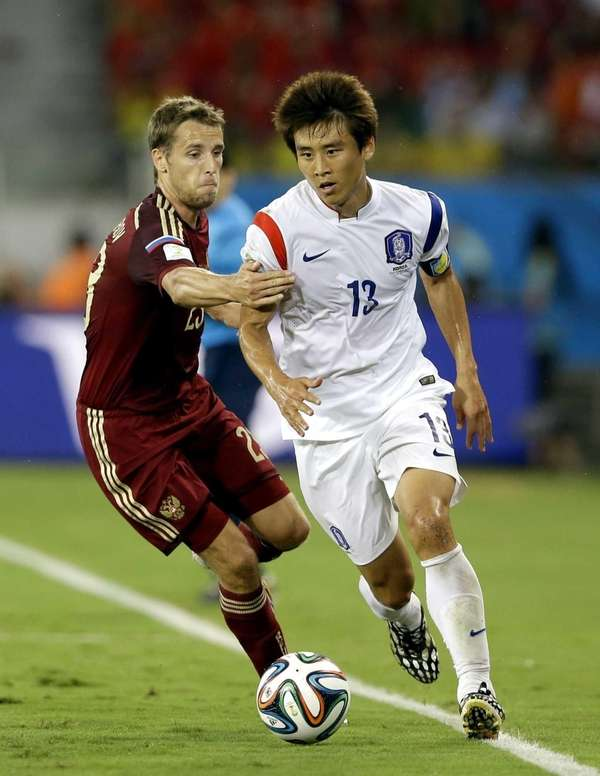 South Korea's Koo Ja-cheol, right, tries to get