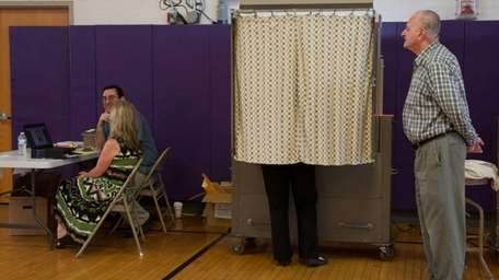 A voter votes on the school budget in