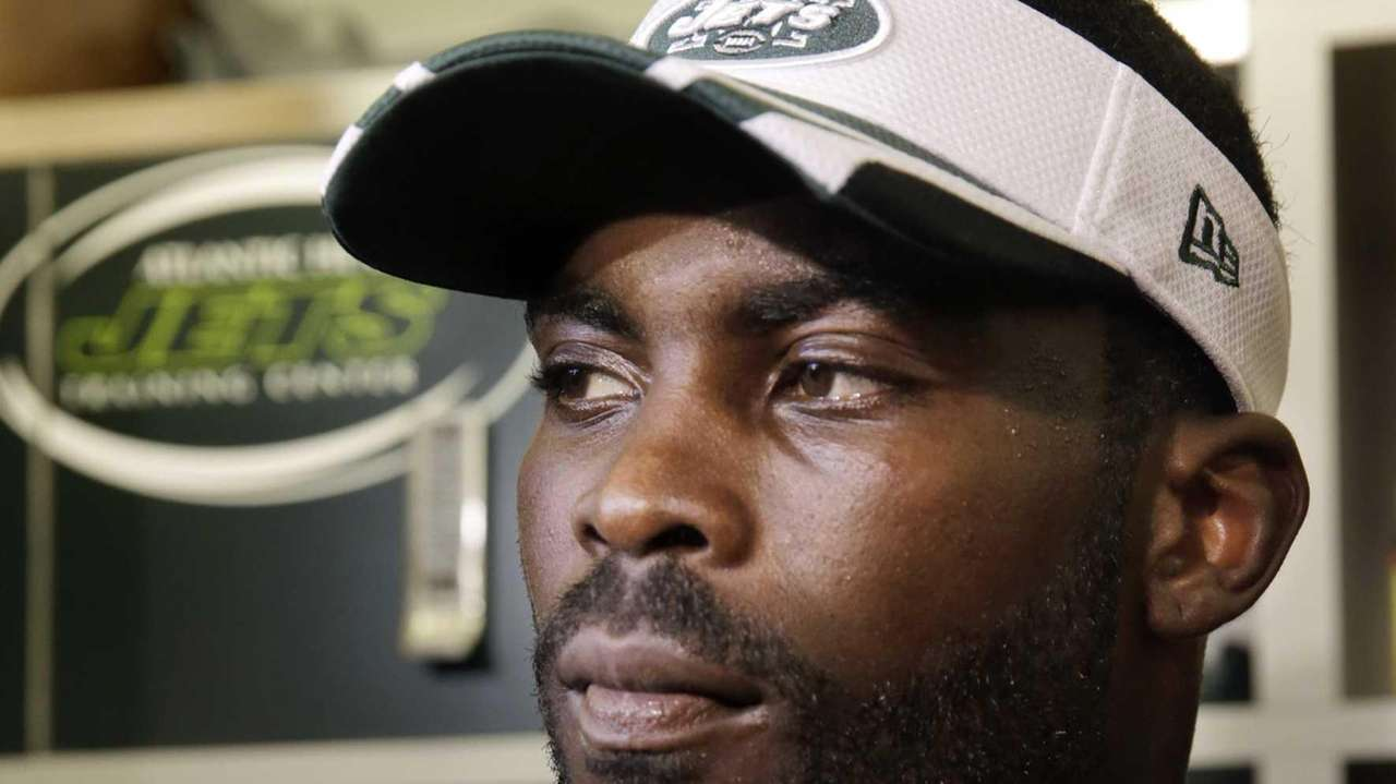 New York Jets quarterback Michael Vick listens to