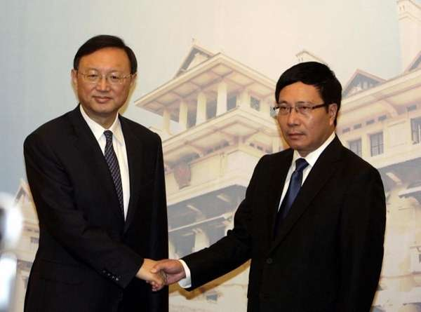 Chinese State Councilor Yang Jiechi, left, shakes hands