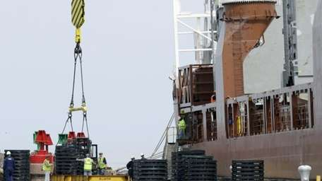 Workers load materials for export onto the Amsterdam-bound