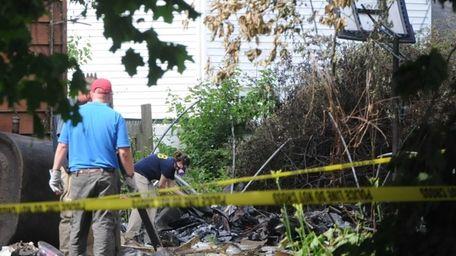 National Transportation Safety Board investigators scour the scene