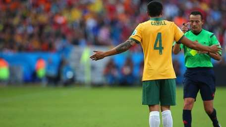 Tim Cahill of Australia is shown a yellow
