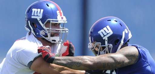 Giants defensive end Damontre Moore, right, takes on