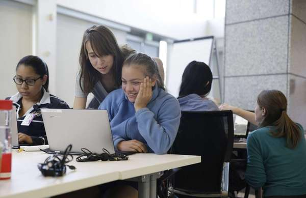 Teacher assistant Margarita Sokolova, second from left, helps