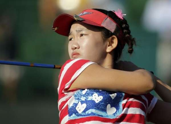 Lucy Li watches her tee shot on the