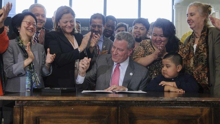 New York City Mayor Bill de Blasio signs