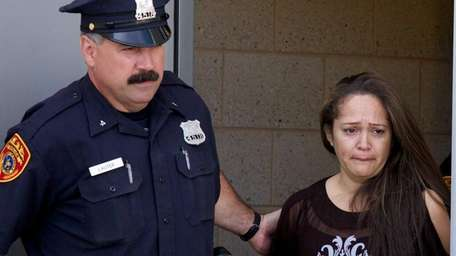 A police officer leads Dorka Lopez out of