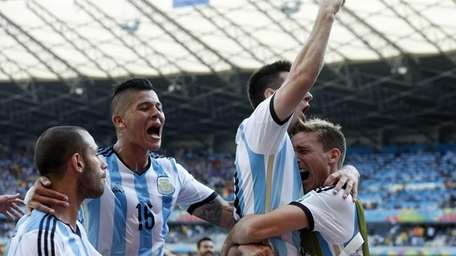 Argentina's Lionel Messi, second right, celebrates after scoring