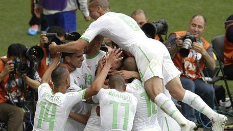 Algeria players celebrate and mob teammate Rafik Halliche