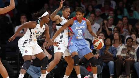 Atlanta Dream's Angel McCoughtry (35) is double-teamed by
