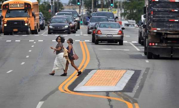 Pedestrians step off a newly-built median strip as