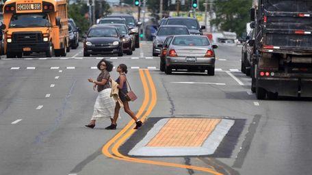 Pedestrians step off a newly-built median strip as