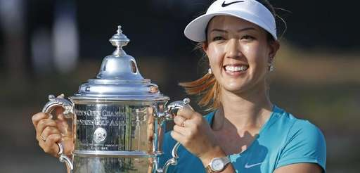Michelle Wie poses with the trophy after winning