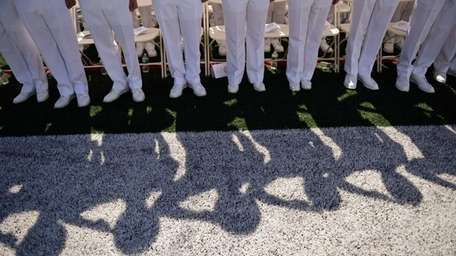 Midshipmen salute during the ceremony as more than
